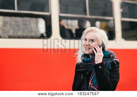 young blonde smiling girl talking on the phone on a background of red train.