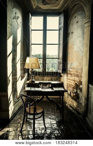 VIGNANELLO, ITALY. November 17, 2015: Room nineteenth century inside the Castello (castle) Ruspoli in the town of Vignanello, Lazio, Italy. Antique desk. Historical lectern in front of a window.