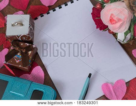 White notebook without inscriptions surrounded by red and pink paper hearts flowers gift box with a ring handle and smartphone