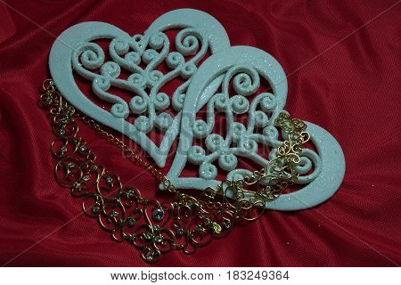 two beautiful openwork carved white hearts on a red background and a gold necklace with precious stones