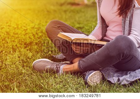 Young girl reading book sitting on green grass in park on meadow. Read and rest