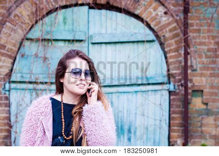 Beautiful girl in sunglasses talking on the phone. Girl with long hair with a smartphone. Woman in a pink artificial fur coat. Young girl on the background of an old door.