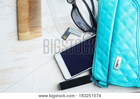 Woman's bag and it's content - phone lipstick sunglasses nail file USB flash drive comb