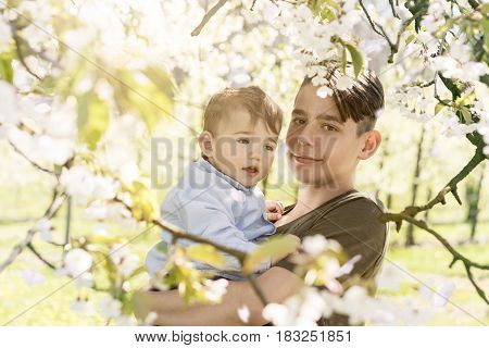 happy teenager boy holding baby at blooming cherry blossom trees