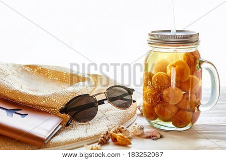 Summer Vacation Concept. Yellow Cocktail Juice With Apricot, Hat, Sunglasses And Shells And Passport