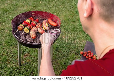 Man Cooking At Grill With Various Delicious Barbecue Outdoor, Selective Focus