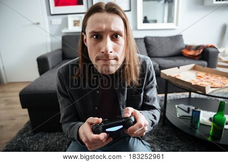 Image of young concentrated man sitting at home indoors play games with joystick. Looking at camera.