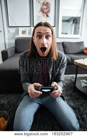 Image of young shocked man sitting at home indoors play games with joystick. Looking at camera.