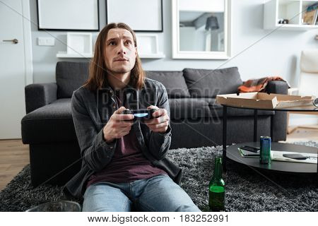 Image of young concentrated man sitting at home indoors play games with joystick. Looking aside.