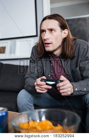 Picture of young concentrated man gamer sitting at home indoors and play games with joystick. Looking aside.