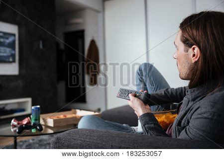 Photo of young man sitting at home indoors eating crisps. Looking aside while watch TV.