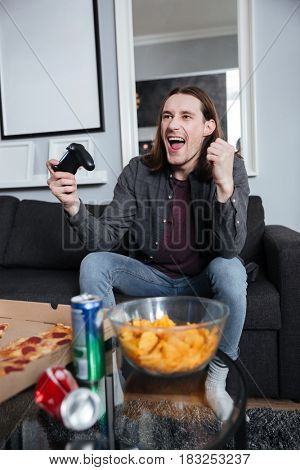 Photo of young happy man gamer sitting at home indoors and play games with joystick. Looking aside.