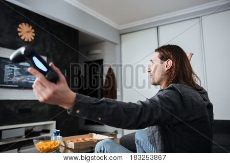 Side view image of young sad man gamer sitting at home indoors and play games with joystick.