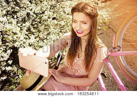 Selfie Girl. Portrait Of Smiling Young And Beautiful Long-haired Girl In Pink Dress Taking Selfie On