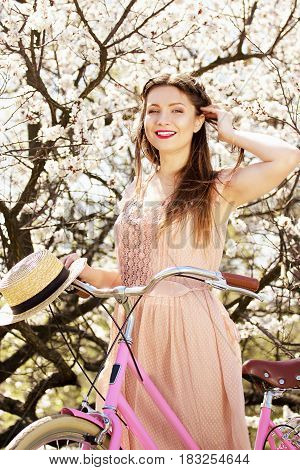 Riding Bike. Portrait Of Smiling Young And Beautiful Long-haired Girl In Pink Dress Standing With Re