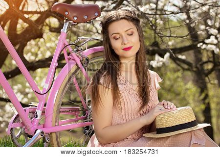 Tender Beauty. Portrait Of Young And Beautiful Long-haired Girl In Pink Dress Sitting Near Pink Bike