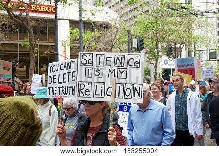 San Francisco CA - April 22 2017: March for Science thousands of protesters march peacefully holding signs in the name of science protesting federal budget cuts that threaten scientific research.