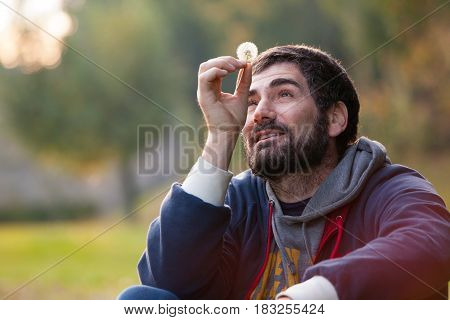 Man completely in love. Lost in mind. Harmony hope and nature. A bearded man holding a dandelion flower in a natural park. He is looking flower with air carefree and in love.