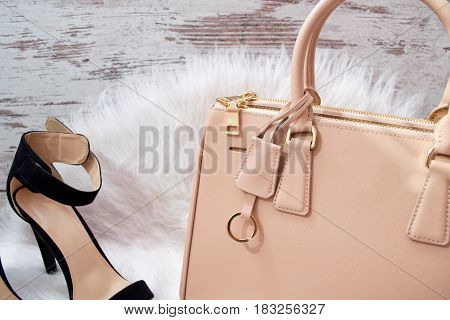 Part of a beige female bag shoes on white fur. Fashionable concept