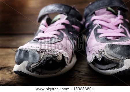 Old worn out shoes with holes and homeless person