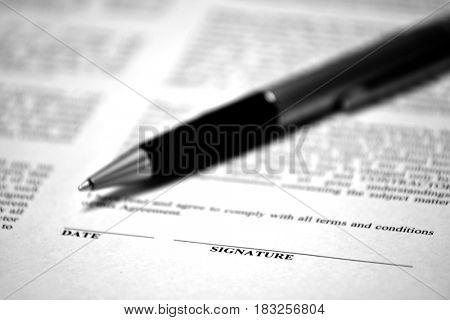Contract on desk with black pen waiting to be signed