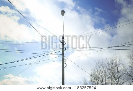 lamppost in the intersection of power lines on blue sky background with white clouds and trees