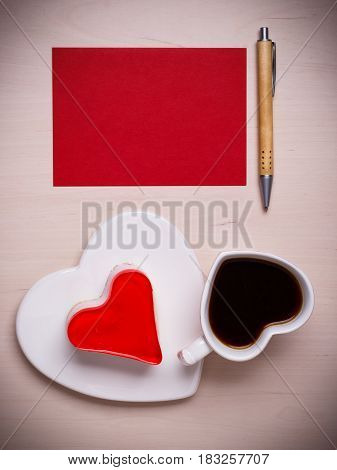 Coffee cup jelly cake in form of heart and red paper blank with pen on wooden surface top view copy space for text