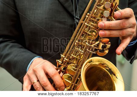 Closeup photography of hands of saxophone jazz player