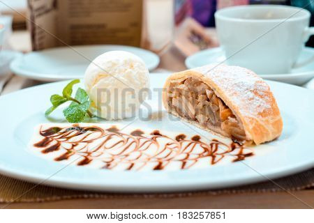 Apple strudel puff pastry on a white plate with vanilla ice cream black & white chocolate spilled on the plate in the form of a nice picture