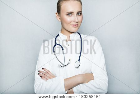 Close up portrait of a young female smiling doctor with nude make up in white gown and with stethoscope on her neck and crossed her arms over her chest on white background.
