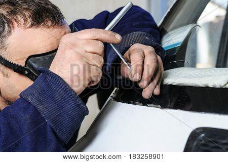 Repair cracked windshield. Car mechanic is repairing cracks in the glass.