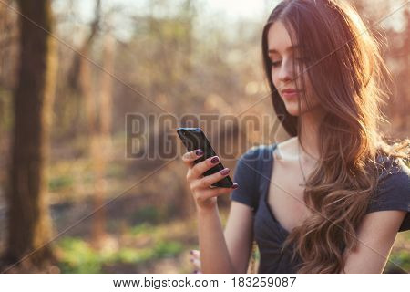 Happy girl reading message using her smart phone in the park. Focus on phone