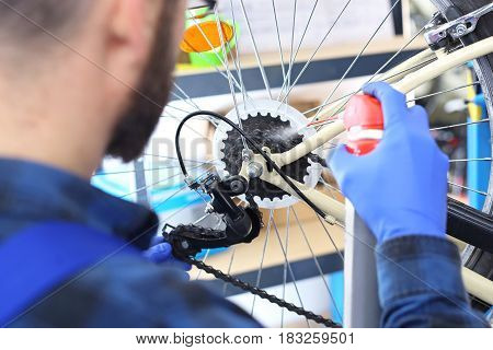 Bicycle service, installation derailleur Man tightens and lubricates the derailleur in the bike Serviceman. The man repairs the bike.