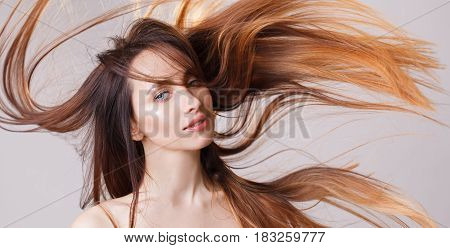 Beautiful model girl with shiny flying brown ombre straight long hair . Care and hair products . Grey background