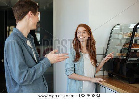 Pretty woman choosing dessert with her boyfriend in cafe