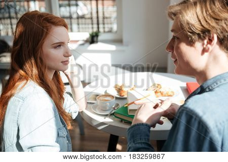 Pretty girl listening her friend student in cafe