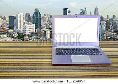 Laptop whit blank screen on long table with Cityscape background, Exterior office.