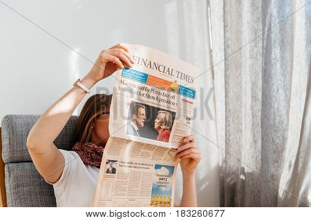 PARIS FRANCE - APR 24 2017: Emmanuel Macron and MArine Le Pen on Financial Times newspaper cover - woman reading the newspaper a day after the first round of the French Presidential election on April 24 2017