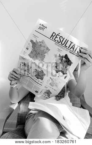 PARIS FRANCE - APR 24 2017: French map electins result on newspaper cover - woman reading the French newspaper Le Monde a day after the first round of the French Presidential election on April 24 2017