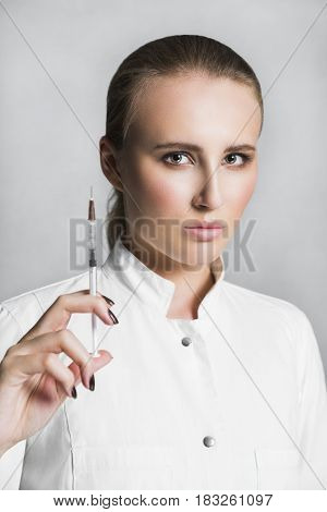 Beautiful blonde female serious concentrated doctor or scientist with nude make up in white medical gown holds a syringe in hand on white background. She is ready to give an injection
