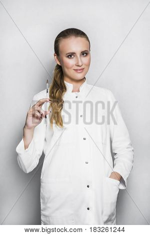 Beautiful blonde smiling female doctor or scientist with nude make up in white medical gown holds a syringe in hand on white background. She is ready to give an injection