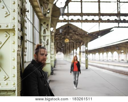 Romantic place for a meet. Stylish beard hipster wait for a girlfriend and look to the camera. Girl run to her boyfriend to go to a trip together by train. Lovers couple on the railway station.