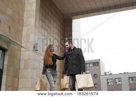 Man and woman after shopping tour stay and talk about new dress in stylish modern street. Girl thank her boyfriend for a interesting weekend. Copy space for advertising text or promotion product.