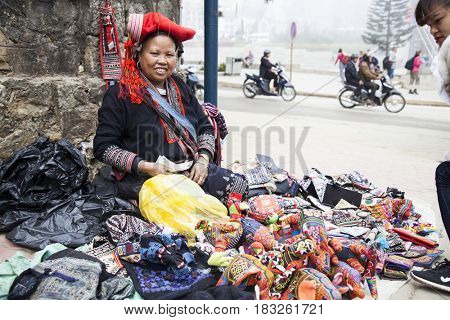 Sa Pa, Vietnam - 15 March, 2017: Woman from Red Dzao minority group wearing traditional attire and headdress selling her goods in Sapa, Lao Cai Province, Vietnam.