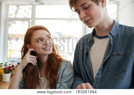 Redhead girl looking at boyfriend while he using tablet in cafe