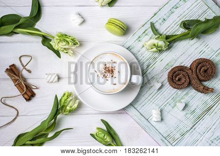 Coffee cappuccino with cinnamon, macaron, marshmallow and beautiful spring tulips on white wooden background
