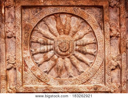 Great example of Indian rock-cut architecture. Ceiling with carved fish inside a wheel of life. 6th century cave temple in town Badami, India.