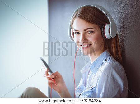 Smiling girl with headphones sitting on the floor
