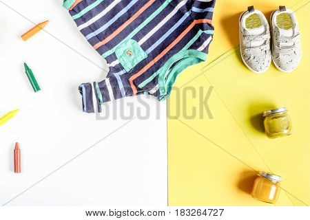 kids desk design with toys and clothes on yellow and white background top view mockup