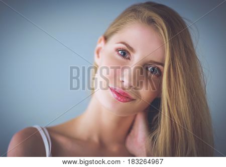 Portrait of beautiful woman isolated on gray background.